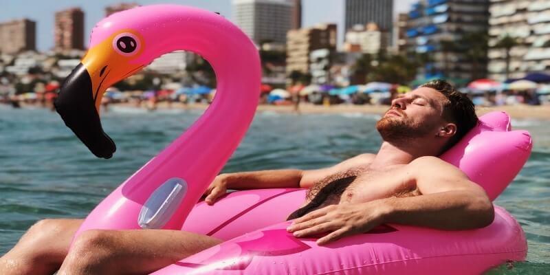 Man sleeping on an inflatable flamingo