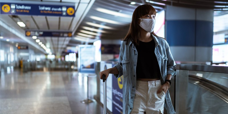woman in a mask standing with her luggage in an airport